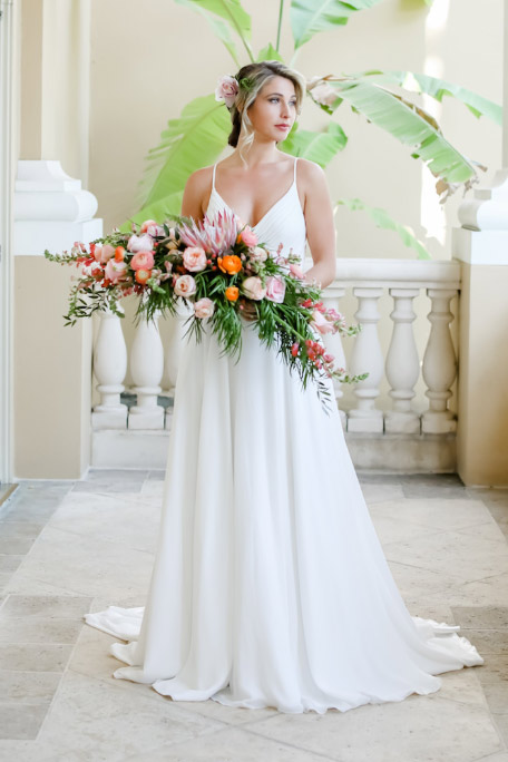 Woman wearing bridal gown holding flowers - Let Us Help You