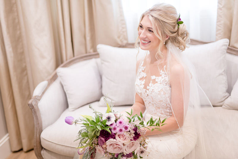 Bride Sitting Down On Couch With Dress Holding Flowers